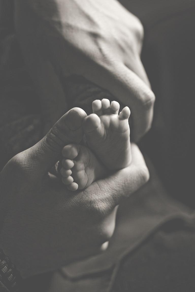 Newborn Pictures dad hands baby feet