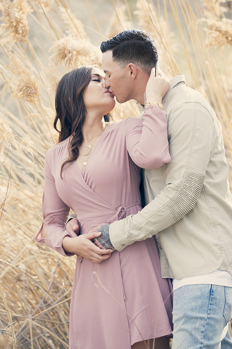 Engagement Photo Kissing in Tall Weeds